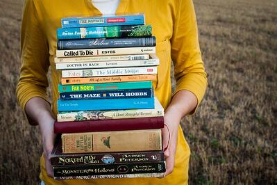 women holding a stack of old books