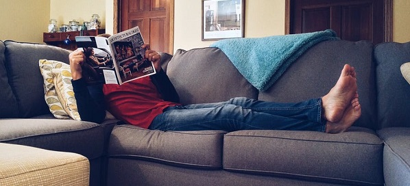 man laying on couch reading magazine