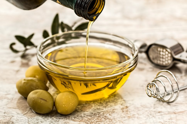 A bottle/bowl of olive oil and olives.