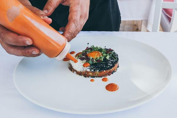 A person adding sauce to a sandwich on a plate.