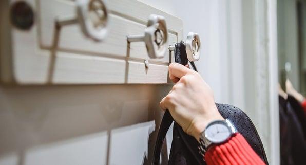 woman handing backpack on hook