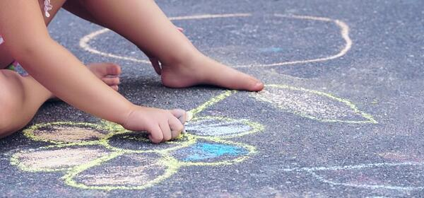 child drawing flowers with chalk on the cement