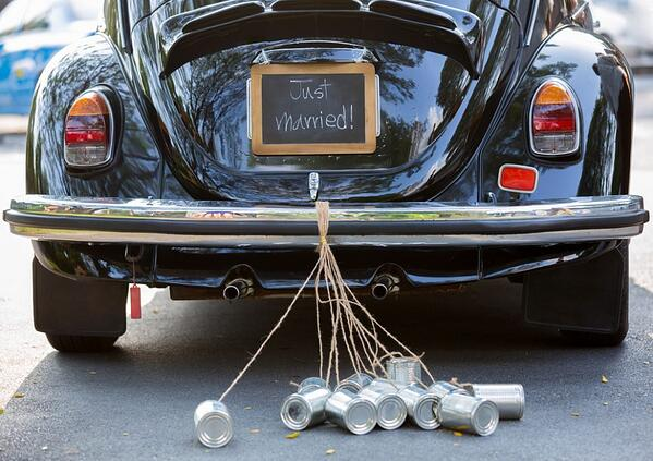 """back of car with """"just married"""" sign and cans tied to the bumper"""