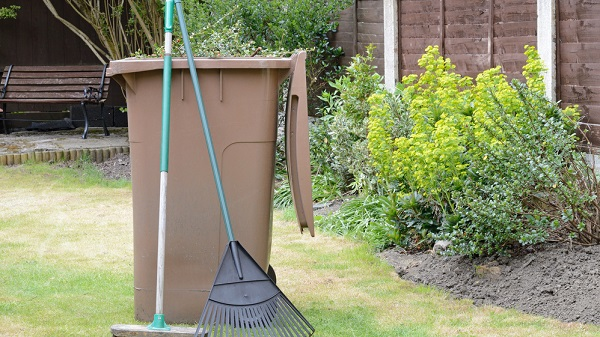 composting container, broom and rake in a yard