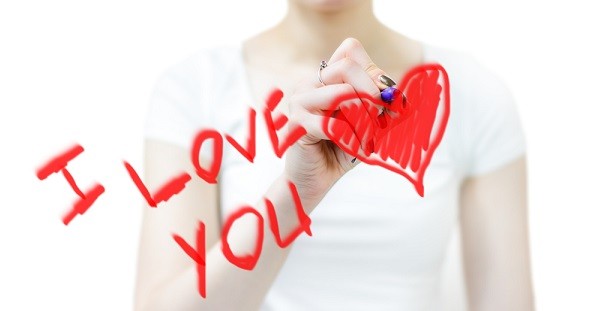 "woman writing ""I love you"" with a heart on a mirror in red pen"