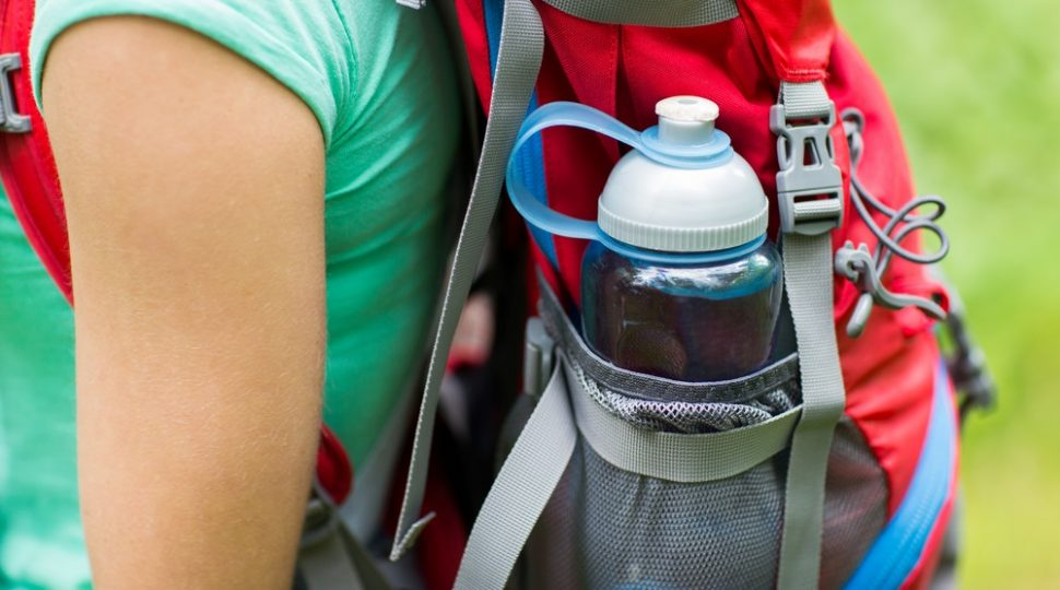 woman carrying a water bottle in a backpack