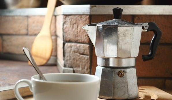 Moka Pot and cup of coffee on table