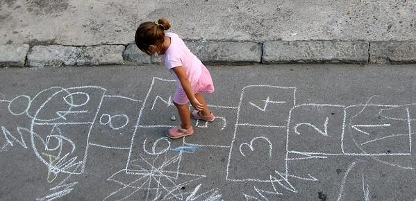 little girl playing hopscotch on the street
