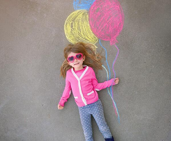 little girl laying in a chalk picture of ballons on the sidewalk