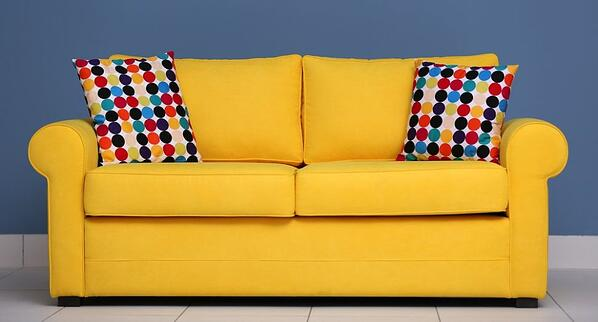Bright yellow sofa with geometric colorful accent pillows