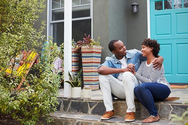 couple sitting on front steps of home