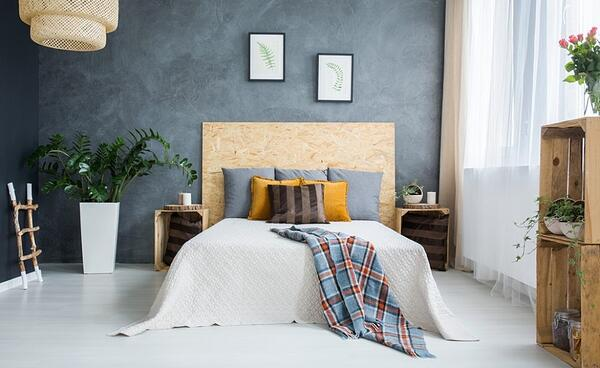 Bedroom decorated with natural materials - concrete wall, wooden headboard, rattan lampshade