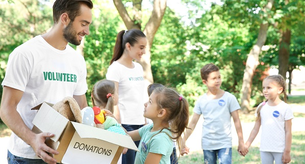 adults and children volunteering to collect donations