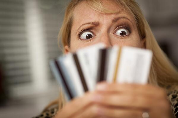 Woman looking at credit cards with a paniced look on her face.